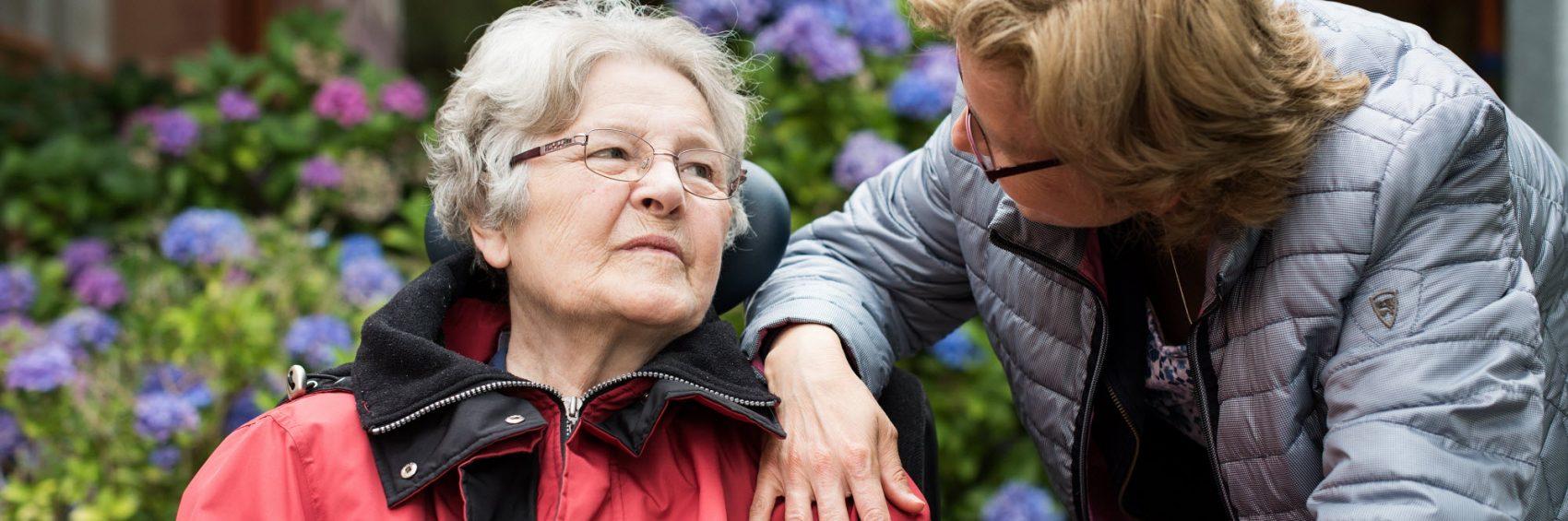 Mantelzorger en dementerende moedere kijken elkaar aan in de tuin van een verpleeghuis