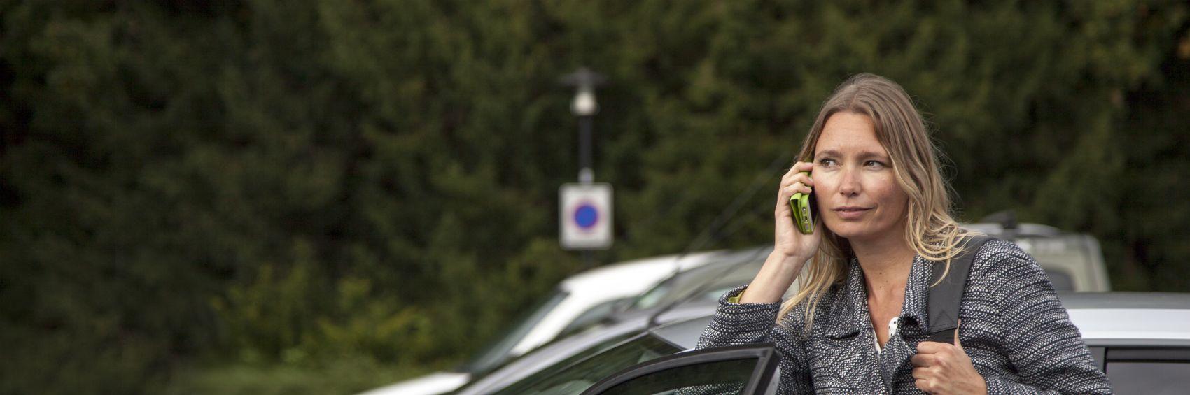 Vrouw aan de telefoon bij auto
